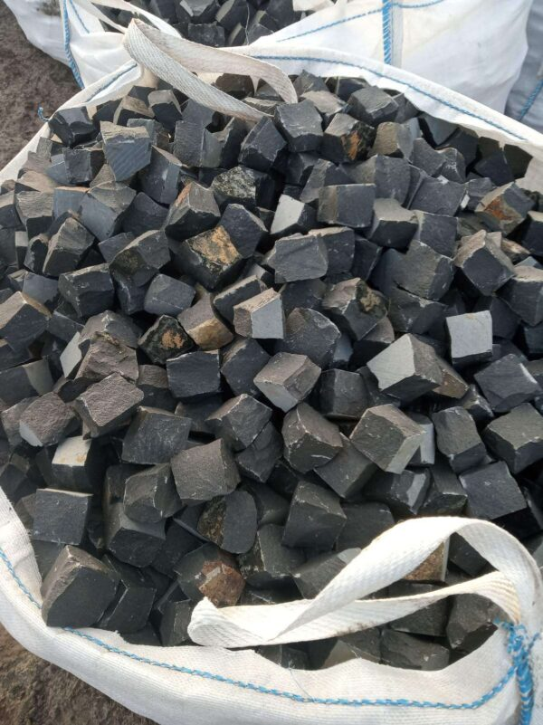 Множество чёрных, упакованных в биг-беги, брусчатых камней из базальта 10х10х5